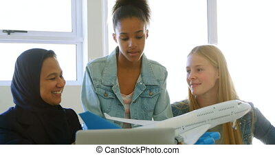 Female pilot giving training about model aeroplane to kids...