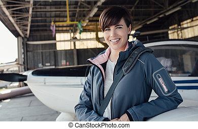 Female pilot posing in the hangar