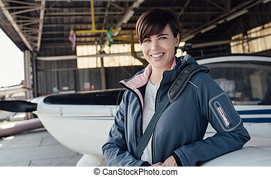 Female pilot posing in the hangar
