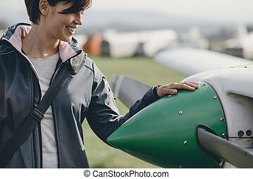 Female pilot posing with her plane
