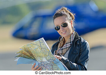 female pilot with map in airplane cockpit