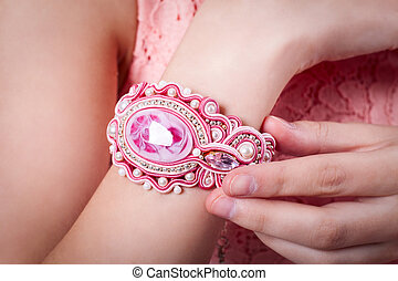 pink bracelet technique soutache on hand of girl in a pink dress, earrings and necklaces