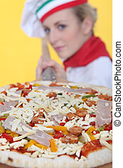 female pizza cook putting a pizza in an oven