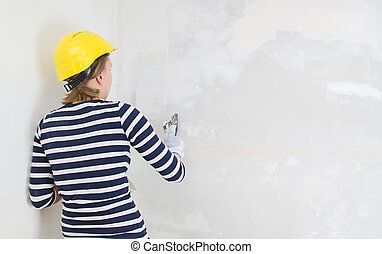 Female plasterer repairs wall with spackling paste. Space...
