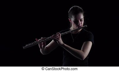 Female plays on the flute classical melodies, professional musician can not be seen in full growth and stands face to viewer, dressed in dark clothes, black isolated studio, slow motion