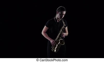 Female plays on the saxophone jazz melody in slow motion