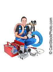 Female plumber crouching by equipment