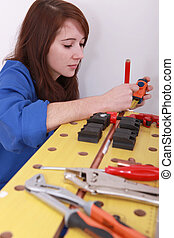 Female plumber cutting copper pipe