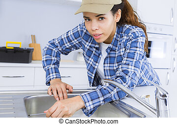 female plumber fixing a sink