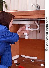 Female plumber repairing sink