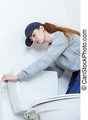 female plumber repairing toilet cistern at water closet