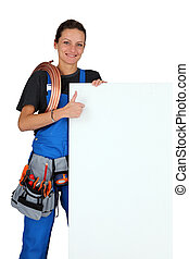 Female plumber with a board left blank for your message