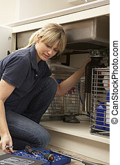 Female Plumber Working On Sink In Kitchen