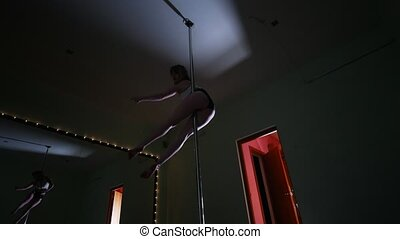 Female pole dancer with sexy shape dancing on a pole in a studio