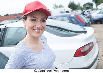 female posing next to a car