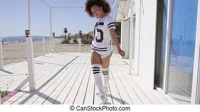 Female posing wearing sportive outfit, white knee-high socks and t-shirt on beach background.