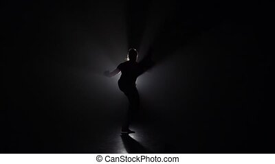 Female practicing capoeira in darkness against light...