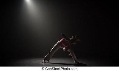 Female practicing capoeira in darkness under spotlight in...