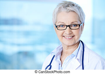 Portrait of pretty female practitioner in eyeglasses looking at camera