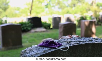 Selective focus of woman hands joining and praying and bending on tombstone with mask kept for deceased relative during coronavirus outbreak