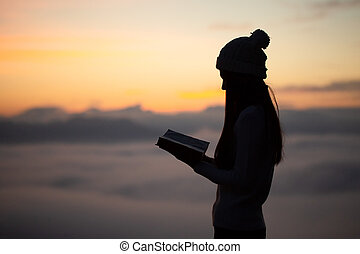 female praying with bible against summer sunrise