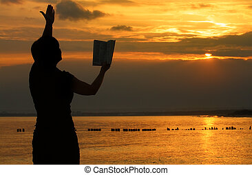 female praying with bible against summer sunset, person isn't identifable