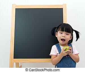Female preschooler with apple in hand