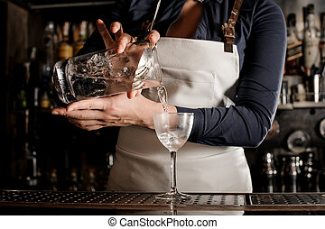 Female professional barman pouring fresh cocktail into a...