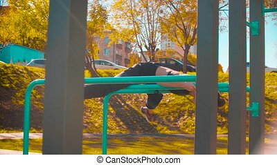 Female professional dancer performing choreographic exercises on parallel bars outdoors. Sunny day, golden autumn