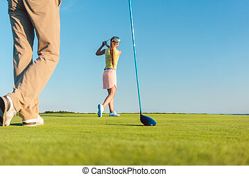 Female professional golfer hitting a long shot during a challenging game