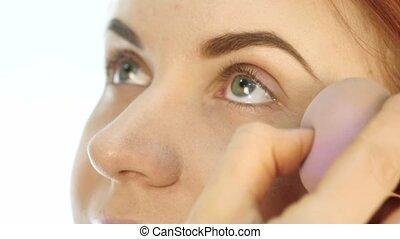 Female professional make-up artist applying cream base ...