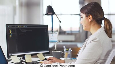 female programmer with computer working at office -...