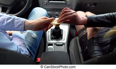 Female prostitute receives payment for her services in the car.