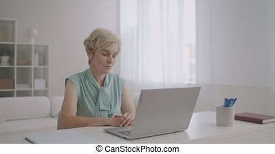 female psychologist is consulting online, talking with client by internet on laptop, distant appointment with specialist during pandemic of coronavirus