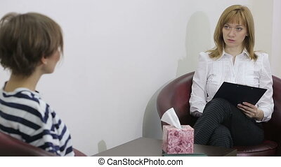 Female psychologist making notes during psychological...