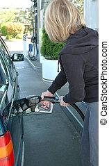 Female pumping gas.