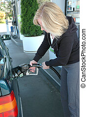 Female pumping gas. - Female pumping gas in her car.