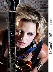 Female punk rocker with her guitar in front of a brick...