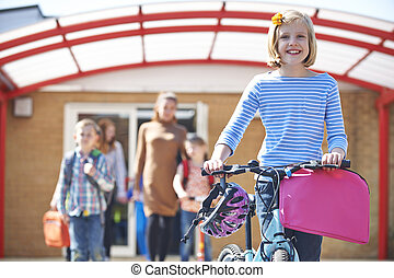 Female Pupil Pushing Bike At End Of School Day
