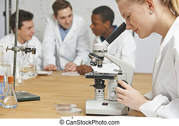 Female Pupil Using Microscope In Science Lesson