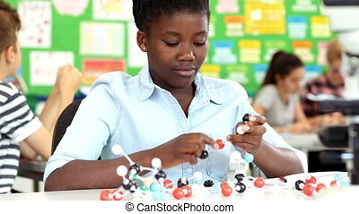 Female Pupil Using Molecular Model Kit In Science Lesson -...