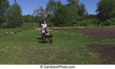 Female pushing little girl in wheelbarrow
