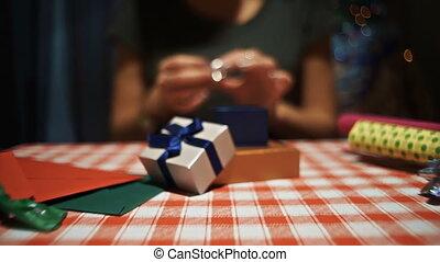 Female putting a silver ring into a small blue secret present box