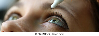 Letterbox view of female putting liquid drops in her eye solving vision problem closeup