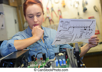 female puzzled in front of electronic parts