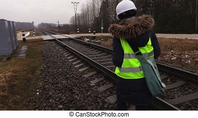 Female railway engineer take pictures of rails before...