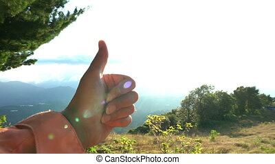 Female Raising hand with thumbs-up on clear blue sky...