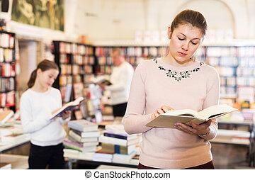 Female reading books in bookshop