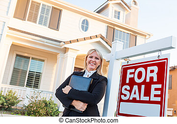 Female Real Estate Agent in Front of For Sale Sign and Beautiful House