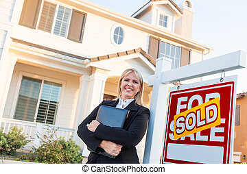 Female Real Estate Agent in Front of Sold For Sale Sign and Beautiful House